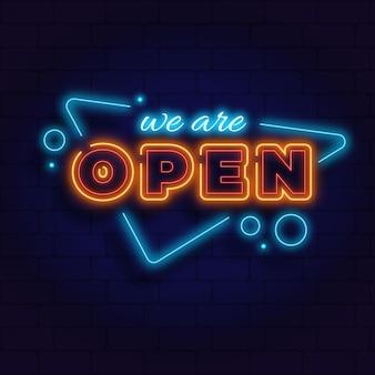 レンガの壁に「私たちは開いています」ネオンサイン