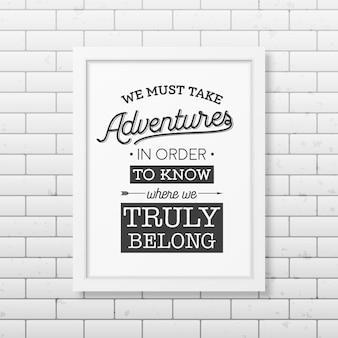 Мы должны отправиться в приключения, чтобы узнать, где мы на самом деле принадлежим - цитата типографский фон в реалистичной квадратной белой рамке на фоне кирпичной стены.