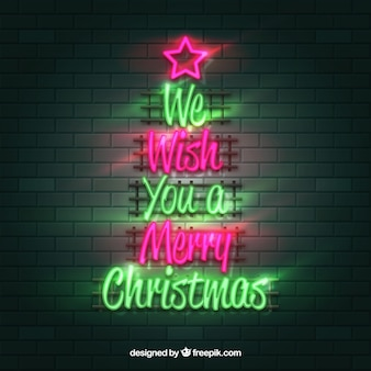 We wish you a merry christmas written in green and pink neon