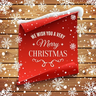 We wish you a very merry christmas, greeting card. red, curved, paper banner on wooden planks with snow and snowflakes.