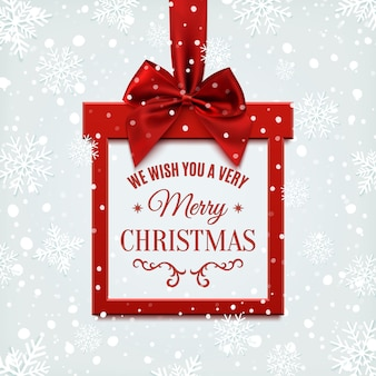We wish you a very merry christmas, square banner in form of  gift with red ribbon and bow, on winter background with snow and snowflakes. greeting card or banner template.