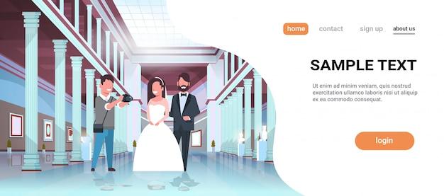 結婚式のカメラマンがカメラで撮影新婚男性の女性が一緒に立っているロマンチックなカップル新郎新婦抱きしめるプロ写真美術館ホール内部水平コピースペースを取って
