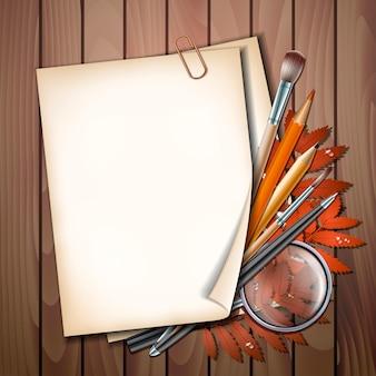 Добро пожаловать обратно в школу. школьные предметы и элементы. лист бумаги с осенними листьями, ручки, карандаши, кисти и увеличительное стекло на деревянном столе