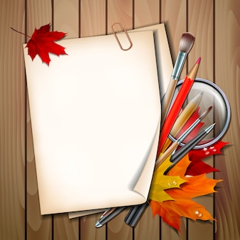 学校の背景へようこそ。学校のアイテムと要素。秋の紅葉、ペン、鉛筆、ブラシ、木製のテーブルに虫眼鏡のある紙