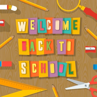 학용품으로 학교 배경에 다시 오신 것을 환영합니다. 다채로운 종이, 콜라주 종이 공예 디자인에서 가위로 잘라낸 단어,