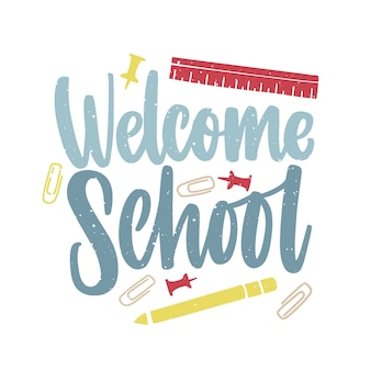 Welcome school inscription handwritten with elegant script and decorated by paper clips, push pins and ruler scattered around.