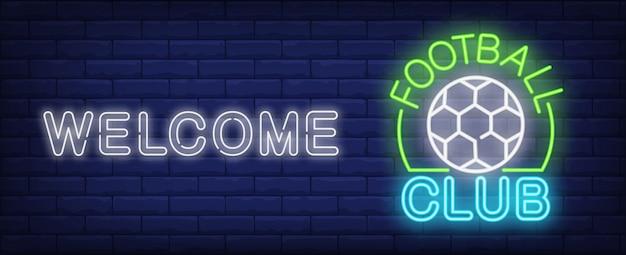 Добро пожаловать в знак неонового знака футбольного клуба. футбольный мяч и светящиеся надписи на темной кирпичной стене