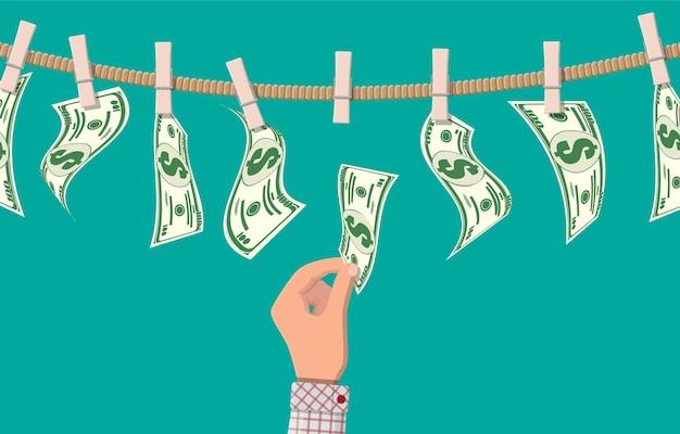 Мокрые долларовые купюры, висящие на веревке, прикрепленной прищепками