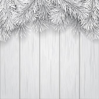 木製の背景に白い人工的なクリスマスツリーの枝。クリスマスグリーティングカードまたは冬のセールバナーのテンプレート。