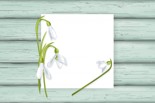 White card with snowdrops on wooden