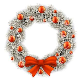 Белый рождественский венок украшен красными шарами.