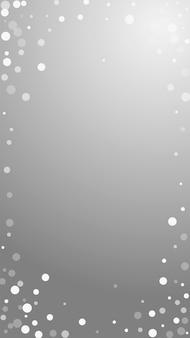 흰색 점 크리스마스 배경입니다. 회색 배경에 미묘한 비행 눈 조각과 별. 실제 겨울 은색 눈송이 오버레이 템플릿입니다. 세련된 세로 그림입니다.