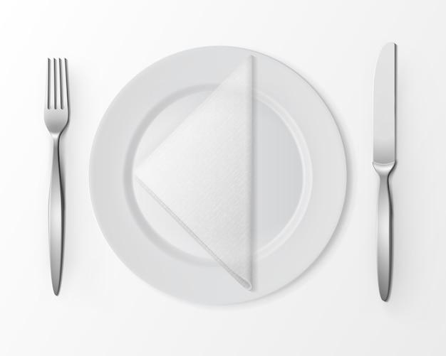 Белая пустая плоская круглая тарелка с серебряной вилкой и ножом и белой сложенной треугольной салфеткой, вид сверху на белом