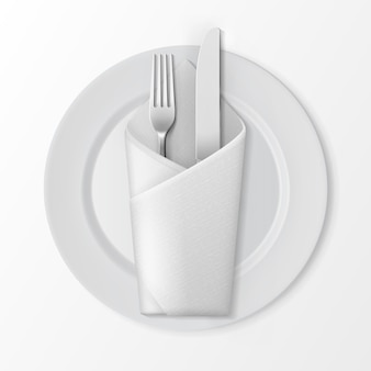 White empty flat round plate with silver fork and knife and white folded envelope napkin top view isolated on white background. table setting