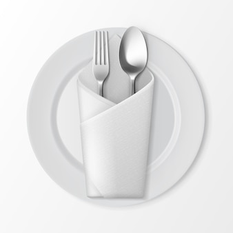 White empty flat round plate with silver fork and spoon and white folded envelope napkin top view isolated on white background. table setting