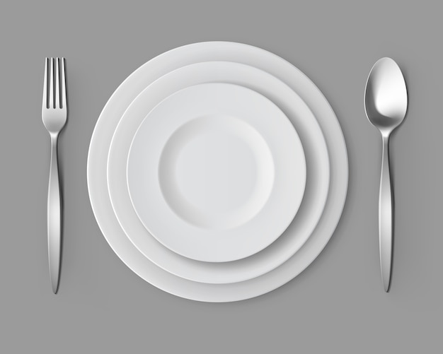 White empty round plates with fork and spoon table setting