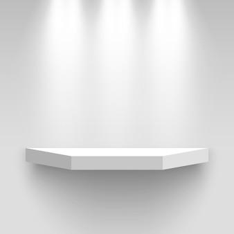 Белый выставочный стенд на стене, освещенный прожекторами. пьедестал. полка.
