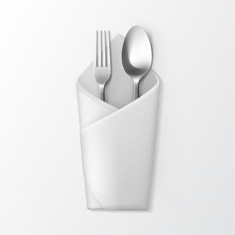 Белая сложенная конвертная салфетка с серебряной вилкой и ложкой сверху на белом фоне. сервировка стола