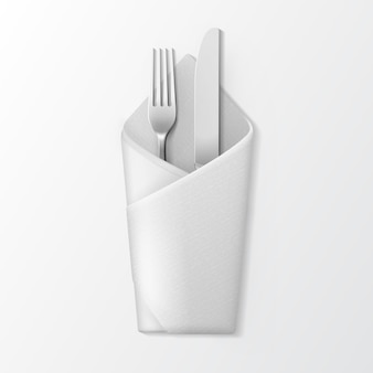 White folded envelope napkin with silver fork and knife top view isolated on white background. table setting