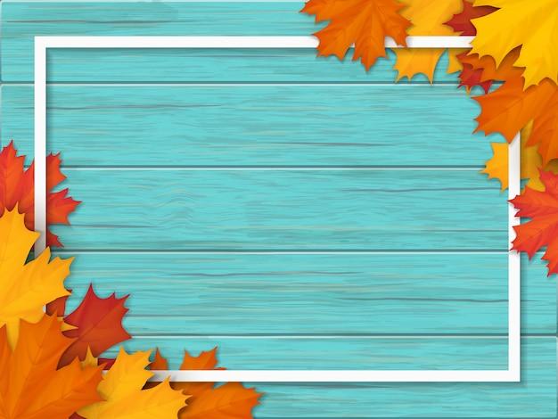 落ちたカエデの葉で飾られた白いフレーム。木製のヴィンテージテーブルの表面の背景に紅葉。