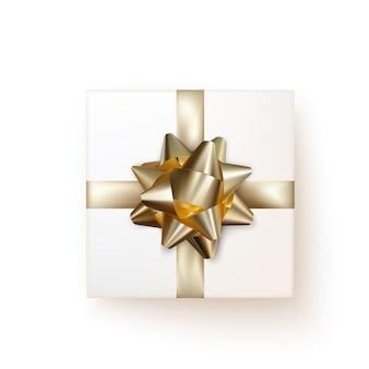 Белая подарочная коробка с золотым шелковым бантом в реалистичном стиле сверху.