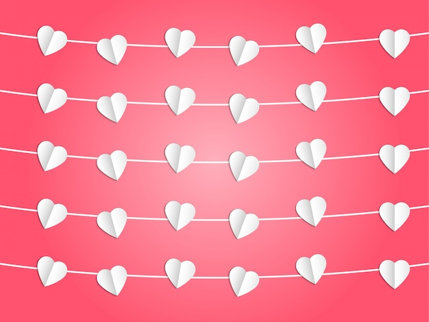 White heart hanging on the rope on pink background