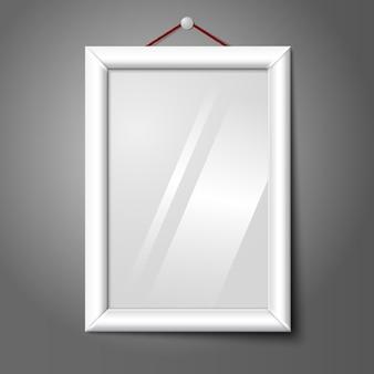 Белая изолированная вертикальная рамка для фотографий, висящая на стене, со стеклом.