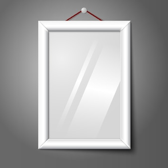 White isolated vertical photo frame hanging on the wall, with glass.