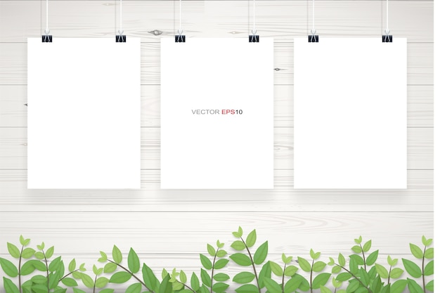 White paper poster hanging on white wooden wall texture background with green leaves frame