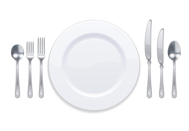 Белая тарелка и серебряные столовые приборы, изолированные на белом