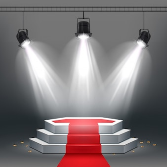 White podium and red carpet illuminated by spotlights