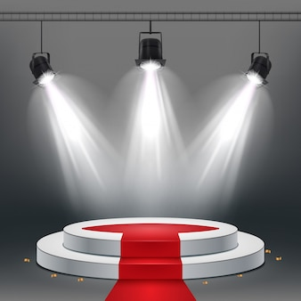 White podium and red carpet illuminated by spotlights