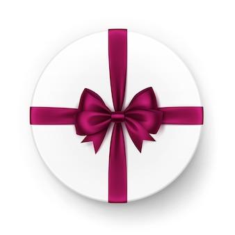 Белая круглая подарочная коробка с блестящим бордово-красным атласным бантом и лентой