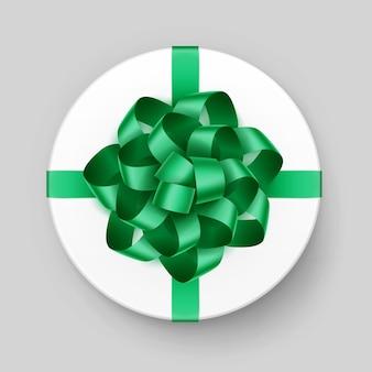 Белая круглая подарочная коробка с блестящим зеленым изумрудным бантом и лентой сверху крупным планом, изолированные на фоне