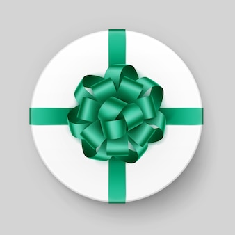 Белая круглая подарочная коробка с блестящим зеленым изумрудным бантом и лентой сверху крупным планом на фоне