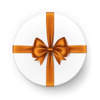 Белая круглая подарочная коробка с блестящим оранжевым атласным бантом и лентой