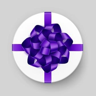 Белая круглая подарочная коробка с блестящим фиолетовым фиолетовым бантом и лентой сверху крупным планом, изолированным на фоне