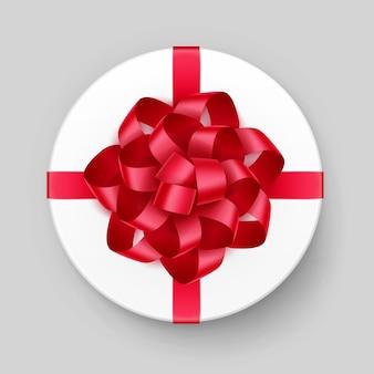 光沢のある赤い緋の弓とリボンの上面図が白い丸いギフトボックスをクローズアップ背景に分離