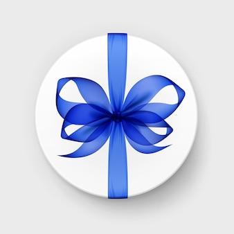 Белая круглая подарочная коробка с прозрачным синим бантом и лентой сверху крупным планом изолированного на фоне