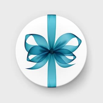 Белая круглая подарочная коробка с прозрачным голубым бирюзовым бантом и лентой сверху крупным планом, изолированным на фоне