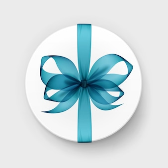 White round gift box with transparent light blue turquoise bow and ribbon top view close up isolated on background