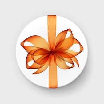 Белая круглая подарочная коробка с прозрачным оранжевым бантом и лентой сверху крупным планом изолированного на фоне