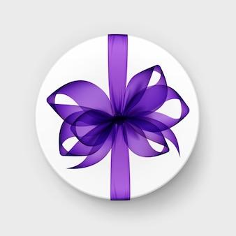 Белая круглая подарочная коробка с прозрачным фиолетовым бантом и лентой сверху крупным планом изолированного на фоне