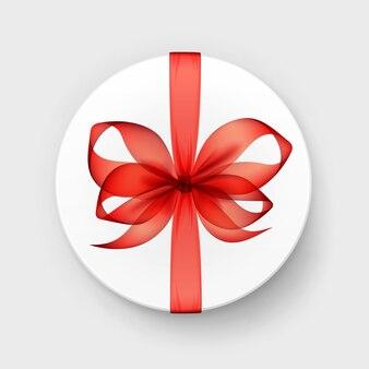 Белая круглая подарочная коробка с прозрачным красным алым бантом и лентой сверху крупным планом, изолированные на фоне