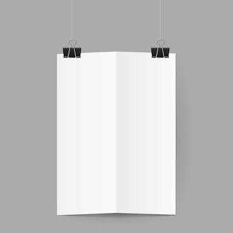 White sheet of paper folded in half handing on black binder clips