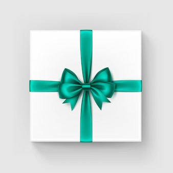 White square gift box with shiny bright green emerald satin bow and ribbon top view close up isolated on white background