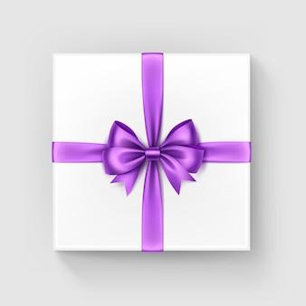 Подарочная коробка белого квадрата с блестящим бордовым светло-фиолетовым сиреневым атласным бантом и лентой, вид сверху крупным планом на белом фоне