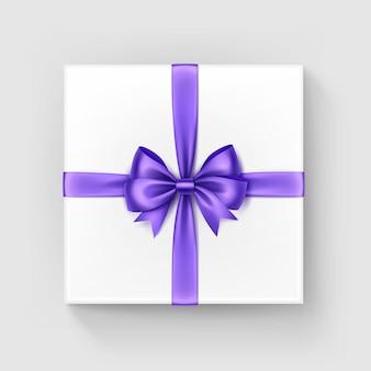 Подарочная коробка белого квадрата с блестящим бордовым фиолетовым фиолетовым атласным бантом и лентой, вид сверху крупным планом на белом фоне