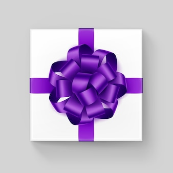 White square gift box with shiny purple ribbon bow close up top view isolated on background