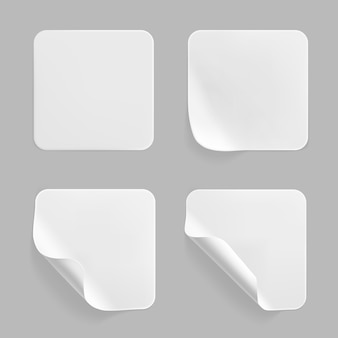 Набор наклеенных квадратных наклеек белого цвета с загнутыми уголками.